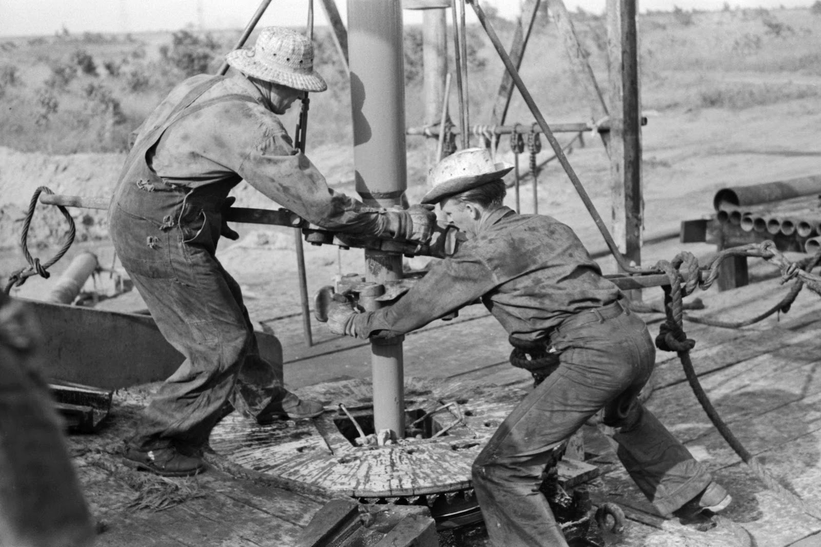 Russell Lee - Adding a length of drilling pipe at oil well in Seminole oil field, Oklahoma. Wrenches applied to loosen pipe, 1939