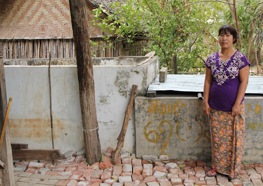 """My house is directly on the fault. The floor of my house was cut by deep fissures. I levelled the ground with bricks from a fallen wall. These wooden posts support my house and used to line up, but have been displaced by dextral slip. The water tank behind me used to be the same height as I am, but subsided during the earthquake."""
